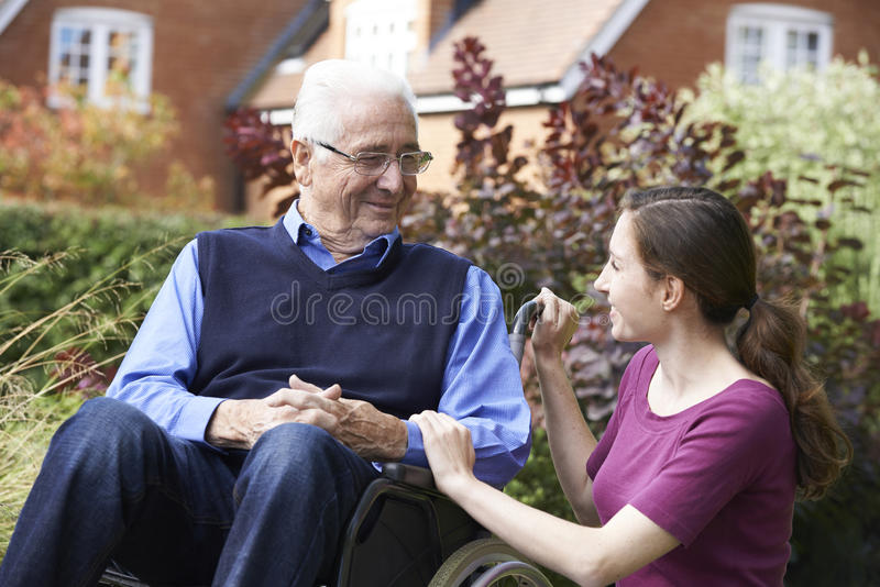 Adult Daughter Visiting Father In Wheelchair. In Garden stock photos