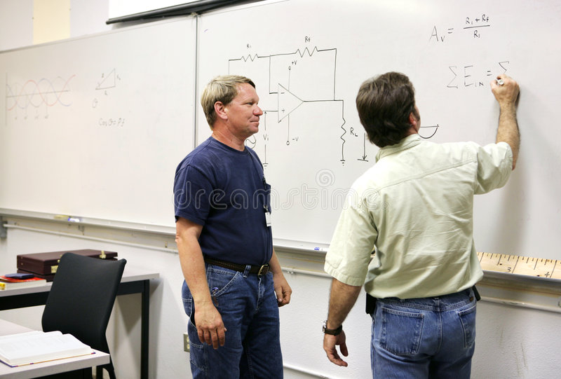 Adult Ed - At the Board. An adult technical college student watching his teacher work equations on the board. Focus on student on left