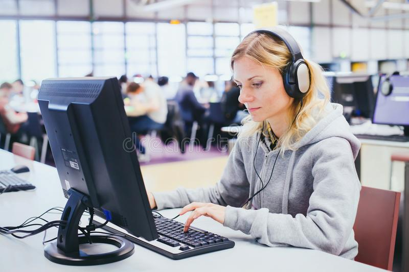 Adult education, middle aged woman studying on computer. In modern library royalty free stock photos
