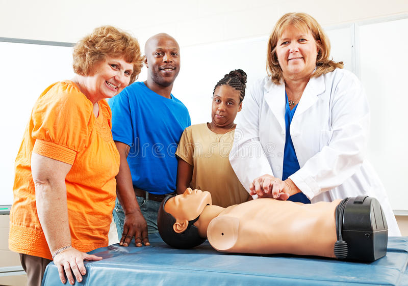 Adult Education Students Learning First Aid. Adult students watching a nurse or doctor perform CPR on a mannequin royalty free stock photo