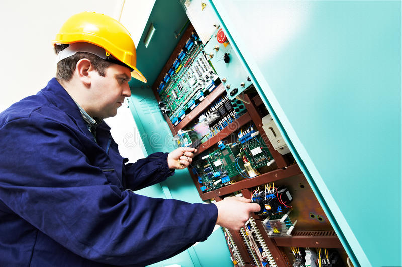 Adult electrician builder engineer worker testing electronics in switch board. Young adult electrician builder engineer worker in front of fuse switch board stock images