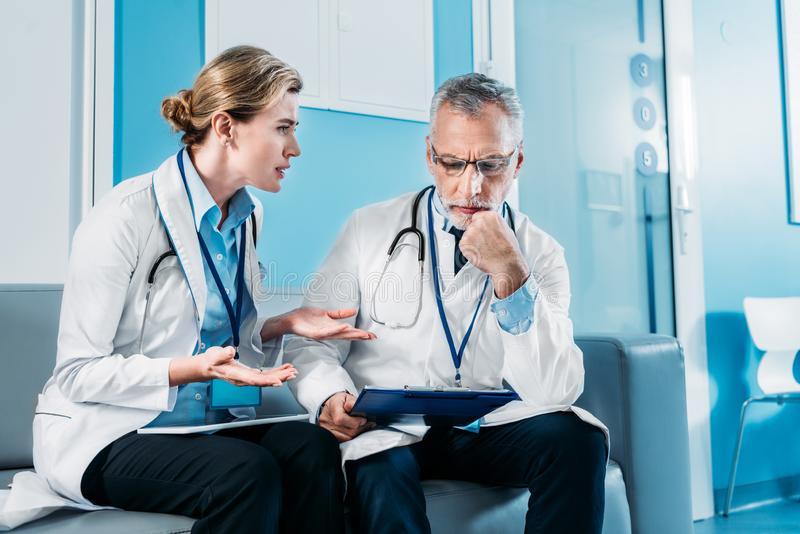adult emotional female doctor gesturing by hands and having discussion with male colleague on sofa in hospital stock photos