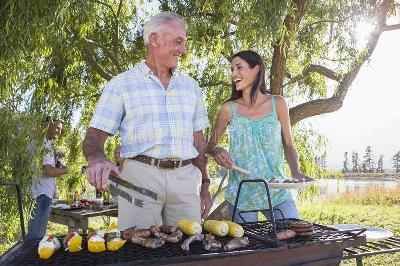 Adult Family Group Cooking Barbeque In Countryside royalty free stock photo