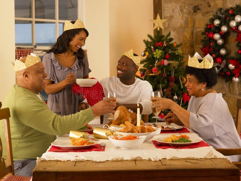 Adult family having Christmas dinner. Adult African American family having Christmas dinner at home stock photo