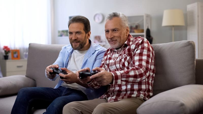 Adult father and son playing video game having fun together, leisure activity stock images