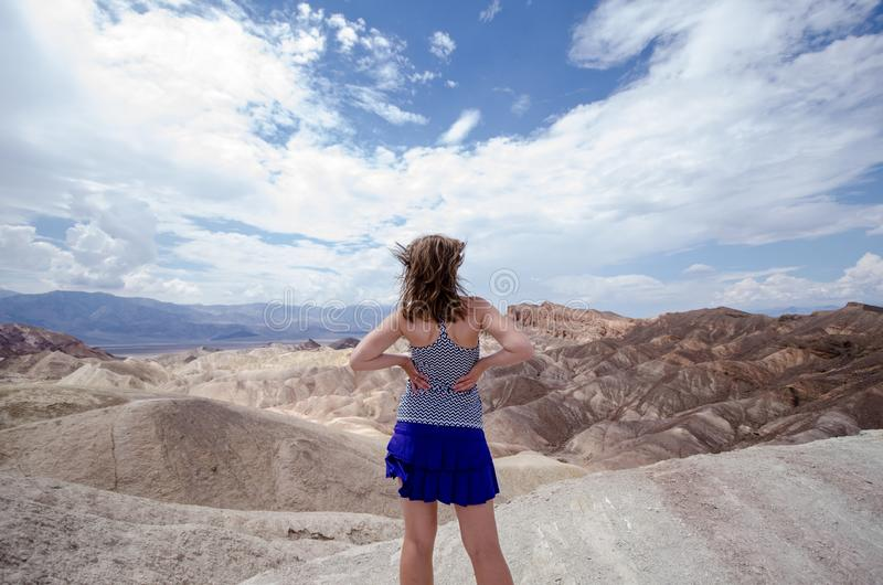 Adult female with back facing the camera at Zabriskie Point in Death Valley National Park, California. Hair blowing in wind on stock photos