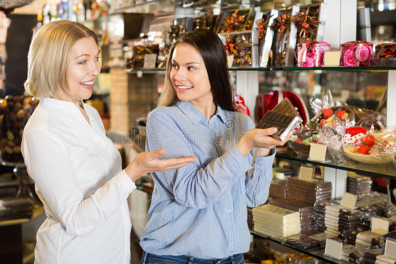 Adult female customers selecting chocolate stock photos