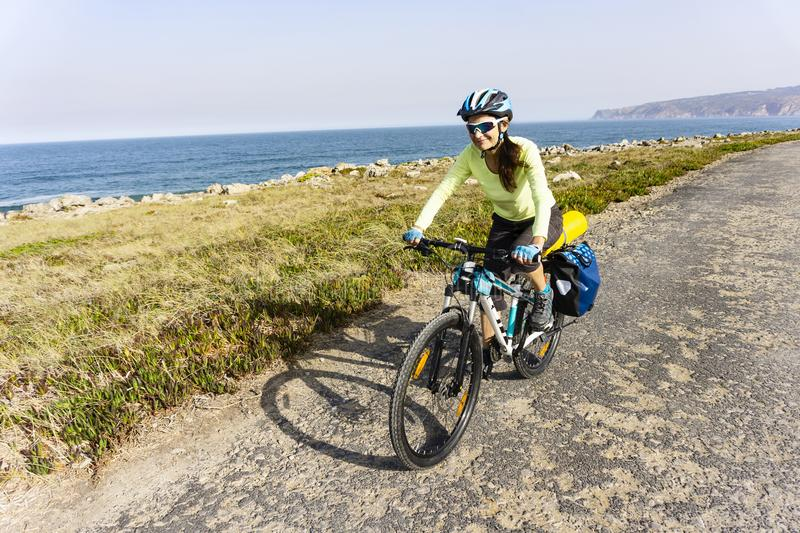 Adult female cyclist rides alongocean shore.. stock photography