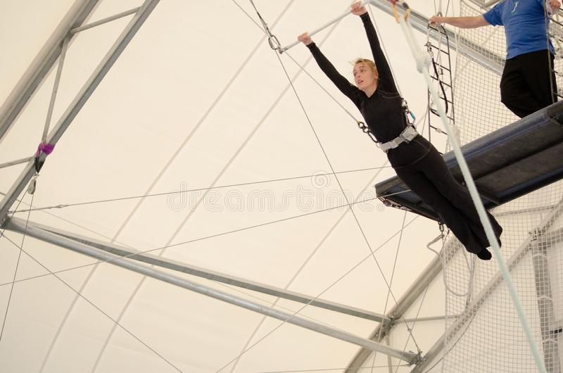 An adult female hangs on a flying trapeze at an indoor gym. The woman is an amateur trapeze artist.  royalty free stock image