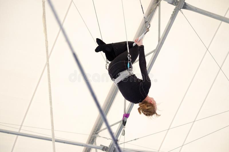 An adult female hangs on a flying trapeze at an indoor gym. The woman is an amateur trapeze artist.  royalty free stock photos