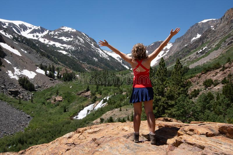Adult female hiker with back facing the camera, and arms raised in Lundy Canyon near Mammoth Lakes in the Eastern Sierra Nevada. Mountain range stock images