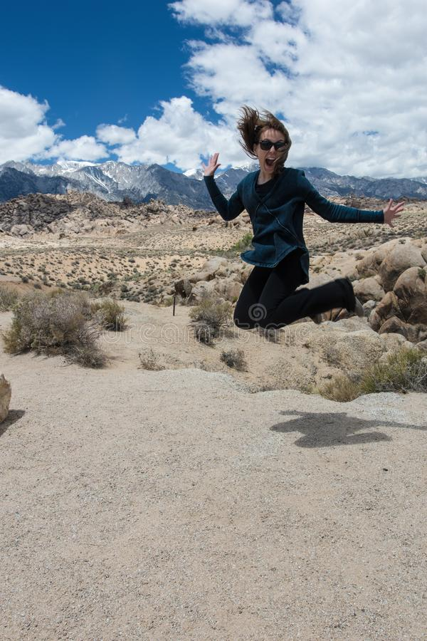 Adult female jumps in a pile of rocks at the Alabama Hills area in Lone Pine California in the Eastern Sierra Nevada Mountains.  royalty free stock photography