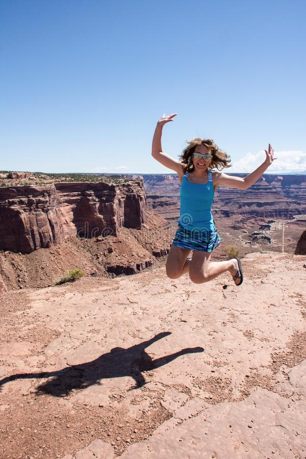 Adult female jumps and smiles at a scenic overlook in Utah Canyonlands National Park on a sunny day. Concept for freedom, stock image