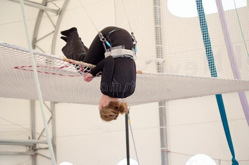 An adult female lands on a net, preparing to dismount at a on a flying trapeze school at an indoor gym. The woman is an amateur. Trapeze artist stock image