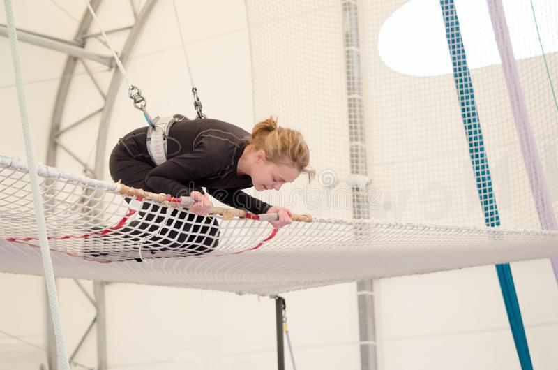 An adult female lands on a net, preparing to dismount at a on a flying trapeze school at an indoor gym. The woman is an amateur. Trapeze artist stock photography