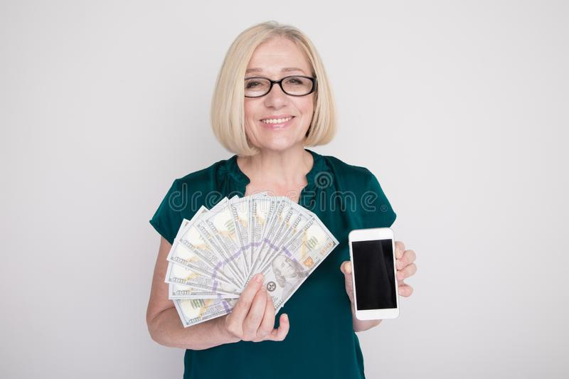 Adult female person holding money and phone in her hands in a white studio. royalty free stock photos