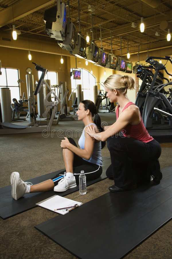 Adult female with personal trainer. Prime adult Caucasian female with personal trainer at gym stock photography