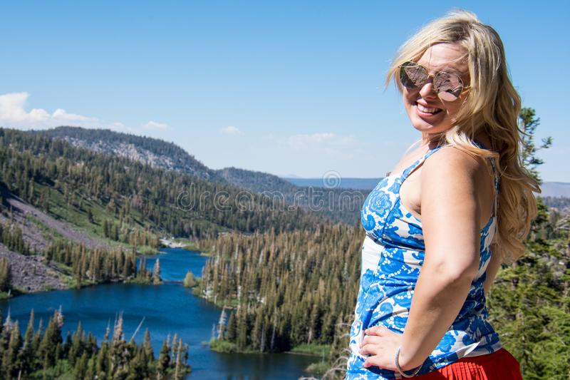 An adult female stands at the top of Twin Lakes overlook in Mammoth Lakes, California, wearing patriotic USA flag colors on the royalty free stock images