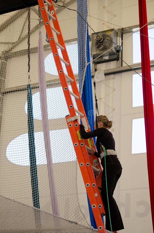 An adult female trapeze artist climbs a ladder leading up to a trapeze platform to perform a jump.  royalty free stock images