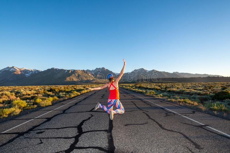 Adult female wearing patriotic American clothing jumps in the middle of a mountain road with her arms raised, concept for freedom. Photo taken in Mammoth Lakes royalty free illustration