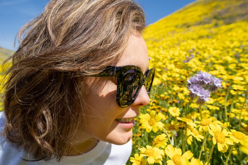 Adult female woman stops to smell the beautiful yellow wildflowers. Concept for springtime allergies royalty free stock images
