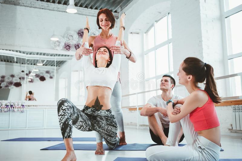 Adult female yoga instructor teaching exercise for group of active people indoor class. Healthe care and lifestyle stock images