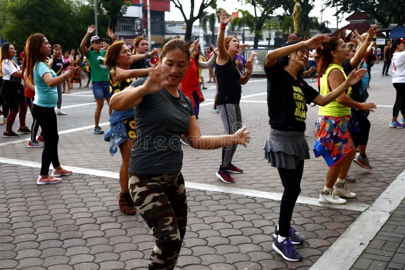 Adult Filipino ladies participate in a Zumba or dance exercise class at a public park. ANTIPOLO CITY, PHILIPPINES – AUGUST 12, 2019: Adult Filipino ladies royalty free stock photo
