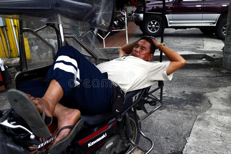 An adult Filipino man rests on his tricycle while waiting for passengers. ANTIPOLO CITY, PHILIPPINES – AUGUST 8, 2019: An adult Filipino man rests on his stock photos