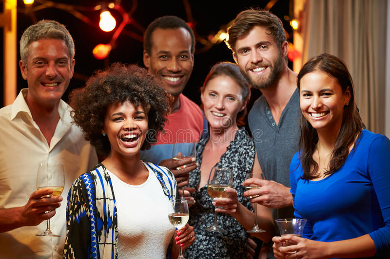 Adult friends drinking at a house party, group portrait royalty free stock image