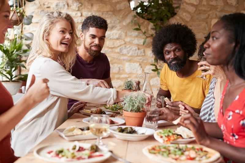 Adult friends eating lunch at a table in a restaurant royalty free stock photos