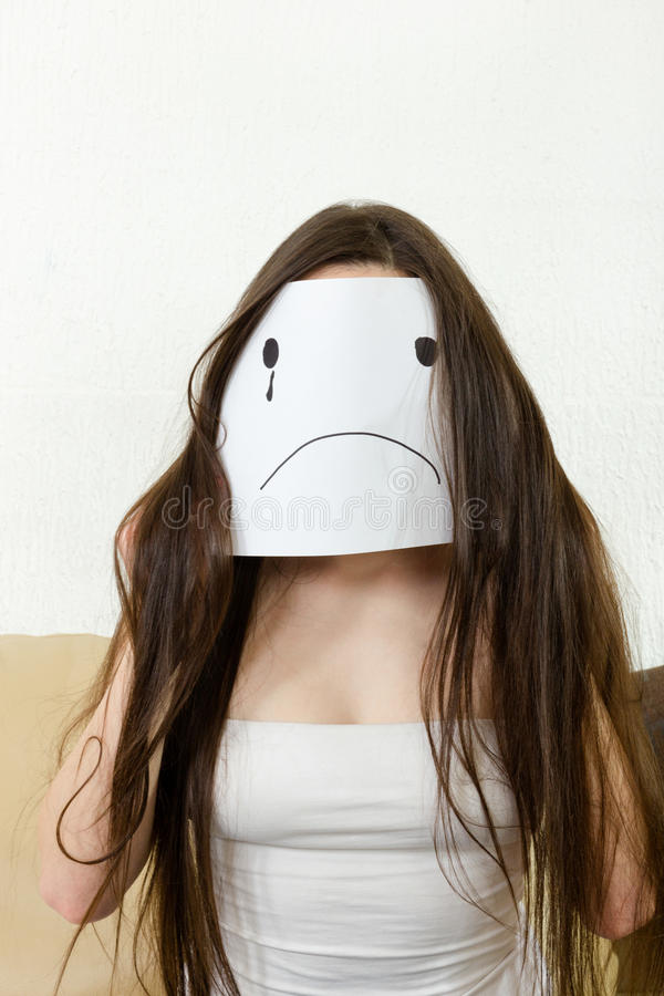 Adult girl cover her face with smile drawn on paper with one tea. Sad woman sitting indoor. Love problems. Financial crisis with money. Adult girl cover her face royalty free stock photo