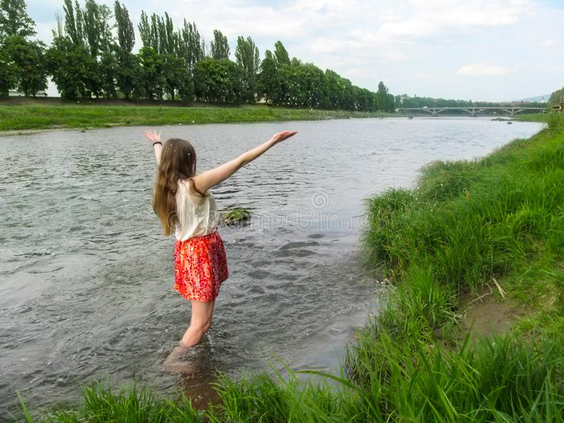 Adult girl with long blond hair splashes in the water of Uzh River - back view. A young woman enjoys spring freshness of water, stock photo