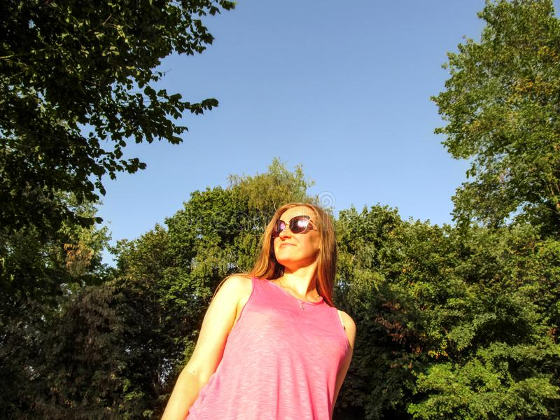 Adult girl with long blond hair in sunglasses looks into the distance, smiling. Portrait of a young woman against the blue sky and royalty free stock images