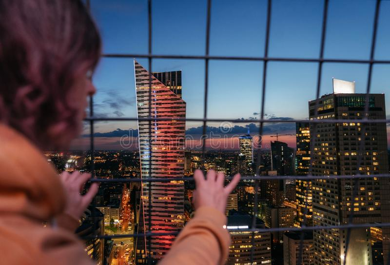 Adult girl looks through metal grid fence at the city at night royalty free stock photo