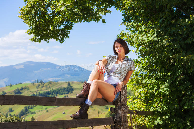 Adult girl sitting on the fence. Countryside fashion style royalty free stock image