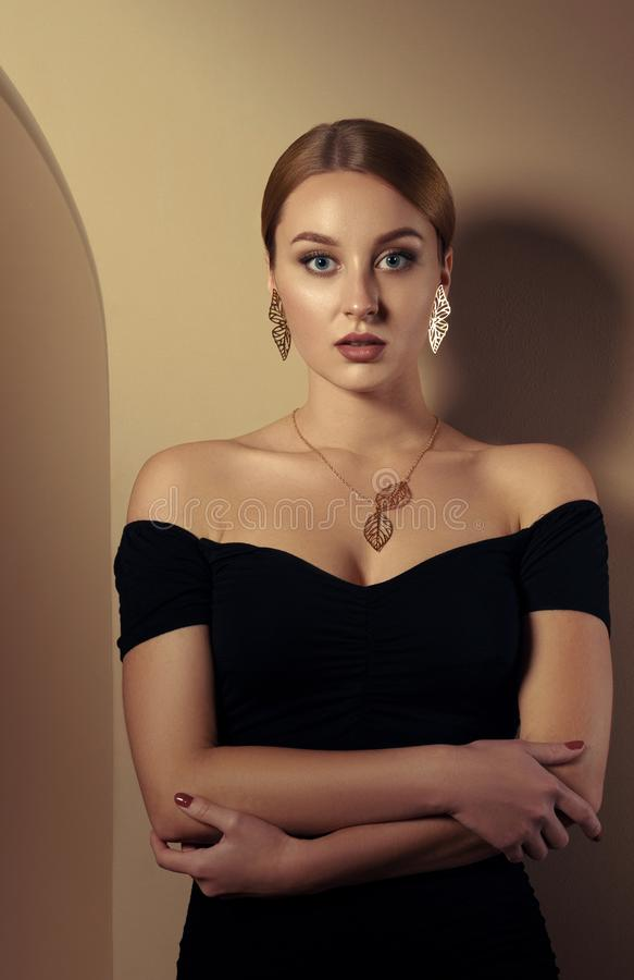 Adult girl wearing nature inspired golden jewelry set and black dress and leaning in beige room royalty free stock images