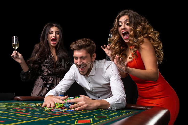 Adult group celebrating friend winning at roulette royalty free stock photo