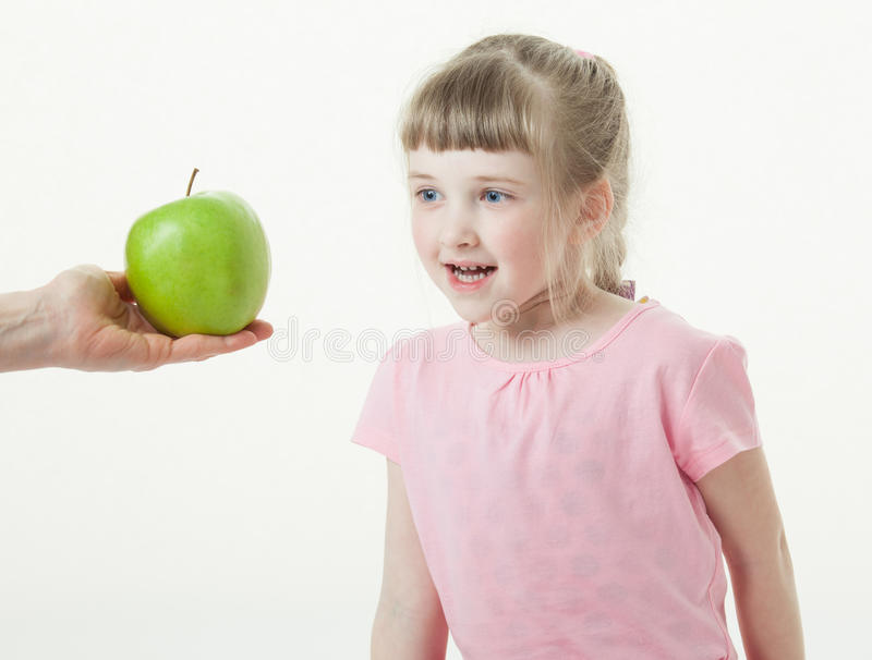 Adult hand giving a green apple for pretty little girl. White background stock photos