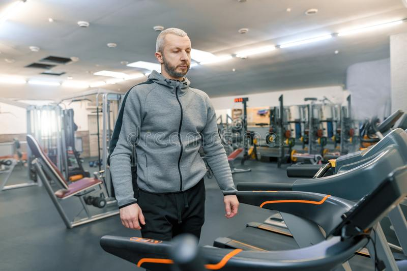 Adult handsome bearded man doing physical exercises in the gym. Sport rehabilitation, age, healthy lifestyle concept. royalty free stock images