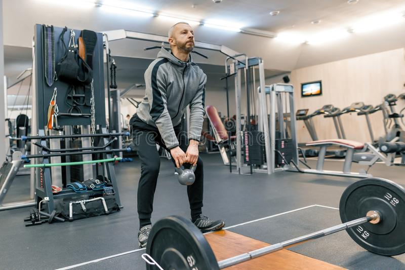 Adult handsome bearded man doing physical exercises in the gym. Sport rehabilitation, age, healthy lifestyle concept stock images