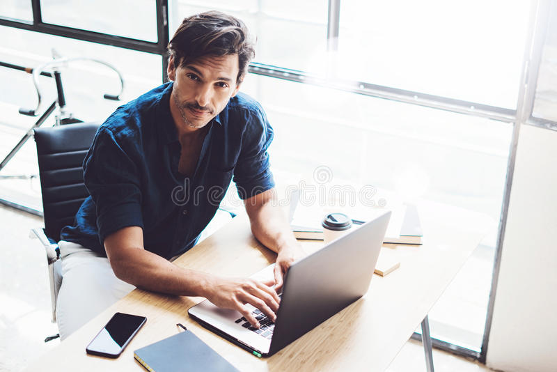 Adult handsome businessman working on mobile computer at sunny office.Coworker typing on notebook keyboard.Horizontal. Blurred background royalty free stock images