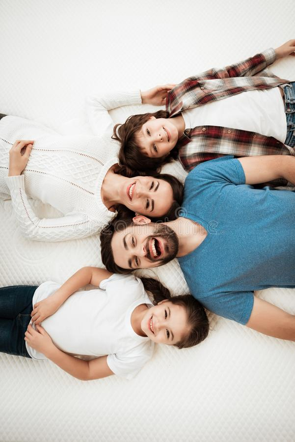 Adult happy couple with cute little son and daughter lies on bed in mattress store. Testing softness of mattress. Check softness of mattress royalty free stock photos
