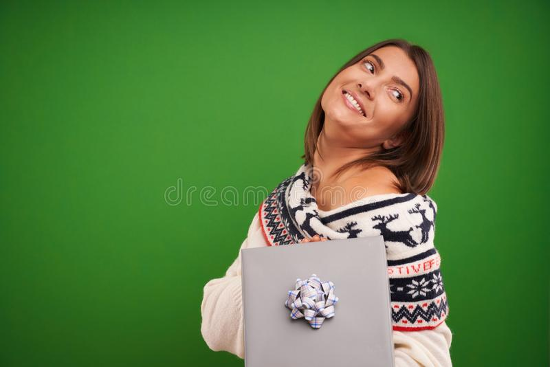 Adult happy woman with Christmas gift over green background stock photo