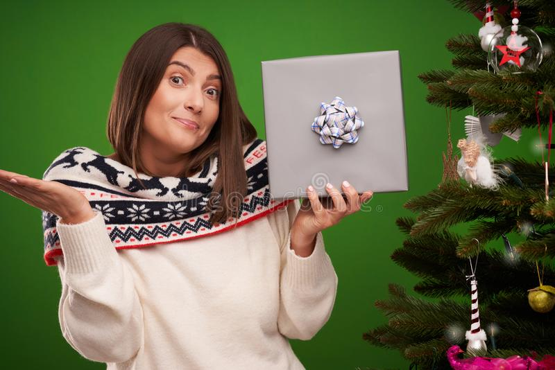 Adult happy woman with Christmas gift over green background royalty free stock image