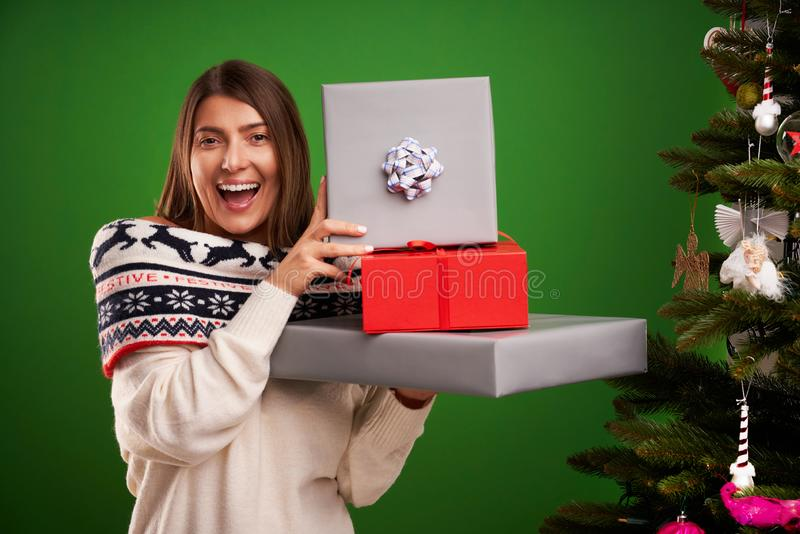 Adult happy woman with Christmas gift over green background royalty free stock photos