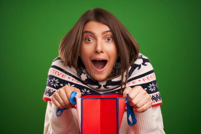 Adult happy woman shopping for Christmas presents over green background royalty free stock image