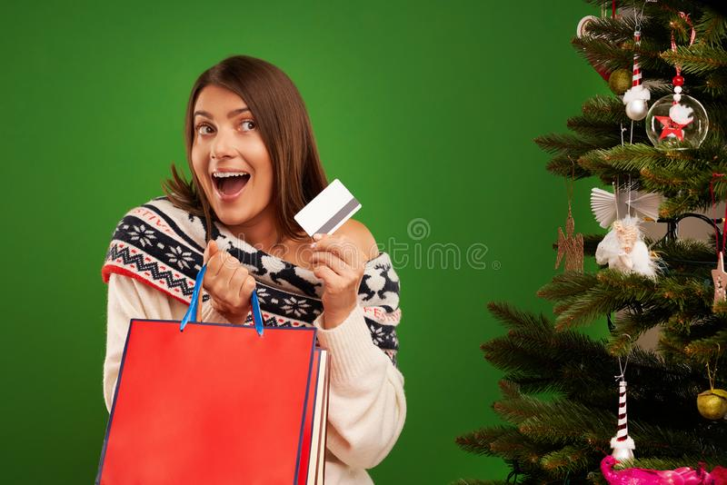 Adult happy woman shopping for Christmas presents over green background stock images
