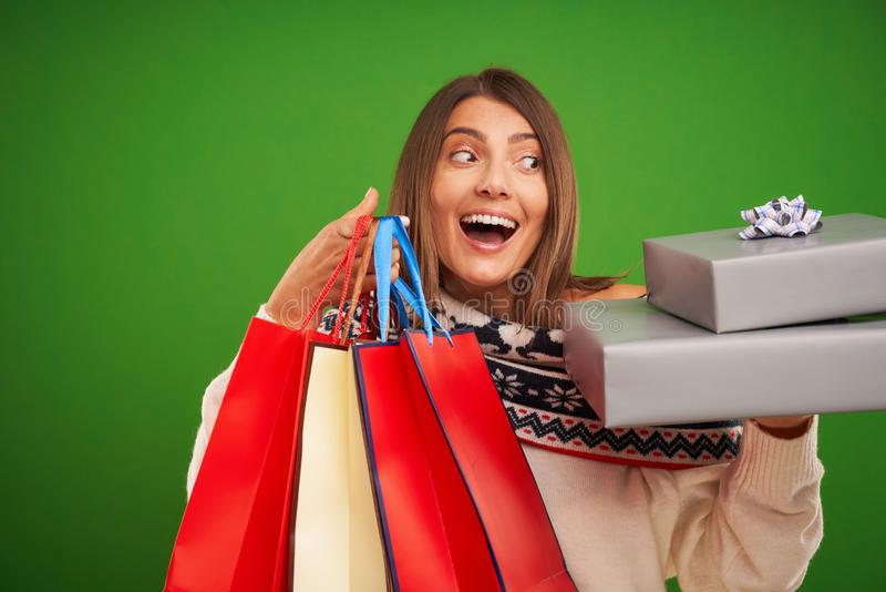Adult happy woman shopping for Christmas presents over green background royalty free stock photo