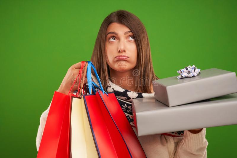 Adult happy woman shopping for Christmas presents over green background stock photography