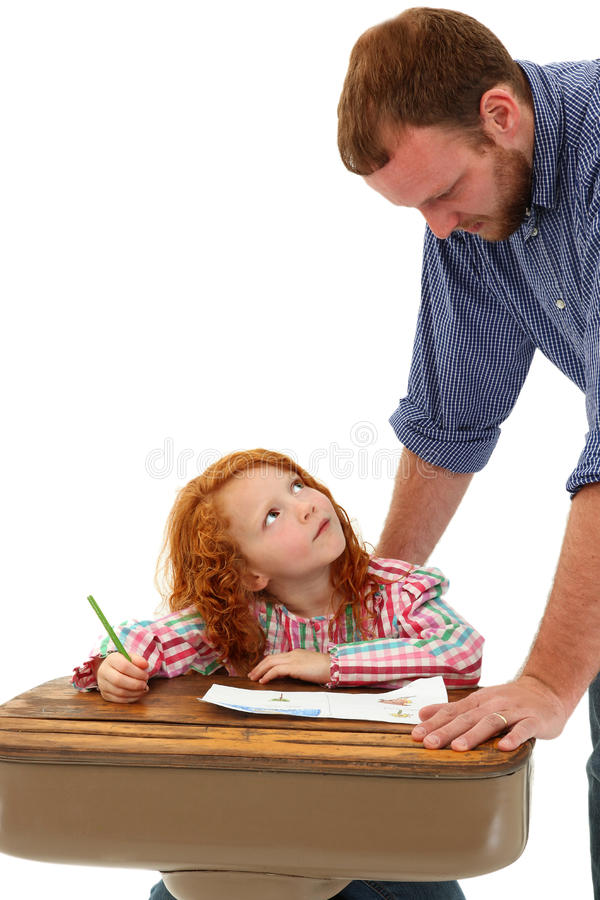 Adult helping School Child at Desk stock images